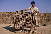 Stacking handmade bricks. Esfahan, Iran.