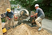 Two builders loading sand with shovel in cement mixer