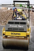 Rolling coated chippings into hot rolled asphalt wearing course using Bomag vibratory roller.