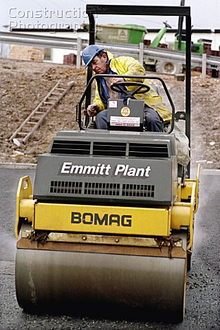 Rolling coated chippings into hot rolled asphalt wearing course using Bomag vibratory roller
