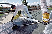 Two workers laying bituminous roofing on a flat roof.