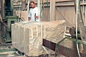 Stonemasonery. Banking work. Working on a piece of stone on a stand.