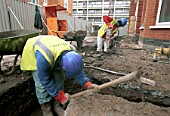 Workers digging a trench during Council Houses refurbishment, East London