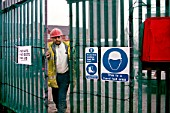 Asian worker at metal site gates showing safety signs.