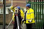 Surveyor using total station on site.