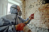 Damp Proofing. Applying chemical treatments with a spray gun.