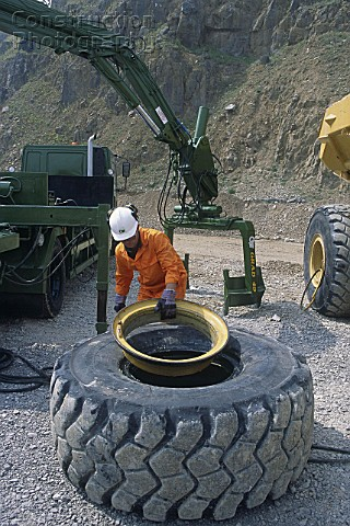 Mechanic changing tyre on heavy duty articulated dumper truck