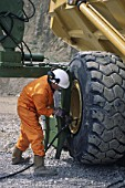 Mechanic changing tyre on heavy duty articulated dumper truck.