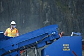 Worker in protective clothing working on crusher at quarry, United Kingdom.
