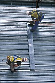 Construction workers cutting and securing steel sheeting.