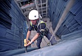 Construction worker abseiling the interior facade of the Kings College new hospital, south London