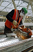 worker cutting steel sheets with a petrol cutter and wearing health and safety protective mask, gloves and goggles.