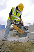 Young builder cutting concrete bricks with a petrol cutter
