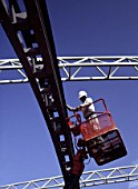 Construction worker on cherry picker inspecting framework.