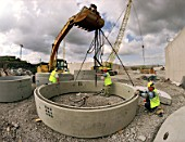 Manoeuvring precast concrete shaft ring at Cardiff waste water treament plant. Wales, United Kingdom.