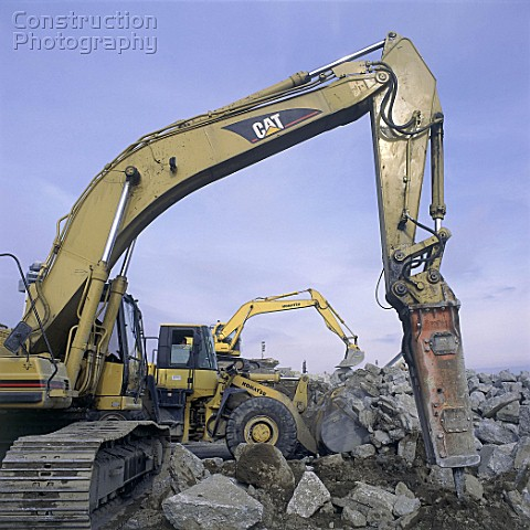 Hydraulic breaker attachment on Caterpillar excavator with Komatsu wheeled loader and excavator in b