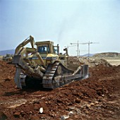 Caterpillar D11N bulldozer using blade and rear-mounted ripper attachment.