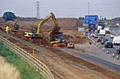 Caterpillar 330B crawler excavator working on slip road link from busy M42 motorway Junction 9 into the M6 Toll road.