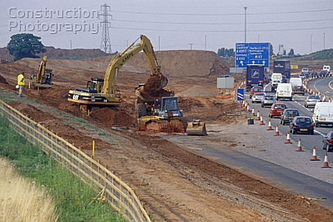 Caterpillar 330B crawler excavator working on slip road link from busy M42 motorway Junction 9 into