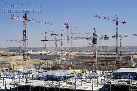Multiple tower cranes on construction site adjacent to Madrid Baracas airport designed by Richard Ro