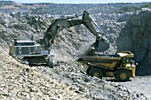 Excavator loading a dumptruck in a quarry.