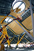 Access platform. Worker on a cherry picker. Working from telescopic platforms on the bamboo interior cladding for the ceiling of the main concourse at architect Richard Rogers new airport terminal for Barajas airport in Madrid, Spain