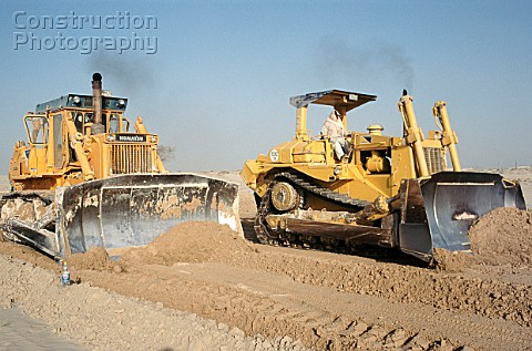 A cat and a Komatsu bulldozer race along levelling the desert ground for road base construction and