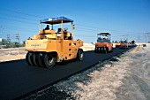 A squad of tyred rollers is used for the finishing work on the asphalt surface of a slip road, Dubai, UAE.