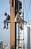 Workers sitting on scaffolding pole. Steel frame work on the Gateway building for the new financial zone, Dubai Finance District, UAE.