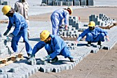 Construction workers laying block paving for container stacking areas, Dubai port Jebel Ali, UAE.