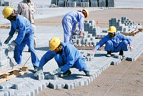 Construction workers laying block paving for container stacking areas Dubai port Jebel Ali UAE