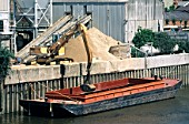 Hanson sand and gravel unloading wharf with a barge of sand being unloaded. Thames river Wandsworth facility.