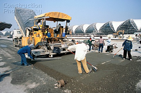Concrete paving machine and crew working on the hardstand areas for the planes near the terminal bui