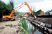 Long reach excavator finishing embankment face on a drainage channel for flood protection in Newport, Wales, UK