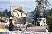 Dump trucks use chalk from the big cutting to build up embankments at the south end of the new A41 Nord near the Swiss border between Geneva and Annecy in France