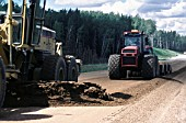 Forest road in northern Alberta is made up using a grader to level fill material followed on by a compactor unit hauled by a tractor - oilsands