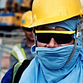 Workers wear clothes under their helmets for projection not against cold but the tropical sun on a site in Singapore