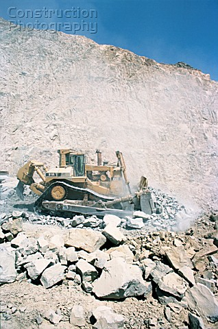 A big Cat D10 bulldozer pushes blasted rock in a deep cutting for the Medina Jeddah highway in Saudi