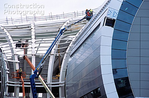 Curved steel frame is worked on from a variety of platforms for the new Dublin airport terminal