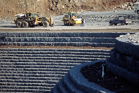 A scraper levels crushed rock fill for a gabion faced stepped embankment forming the approach to a t