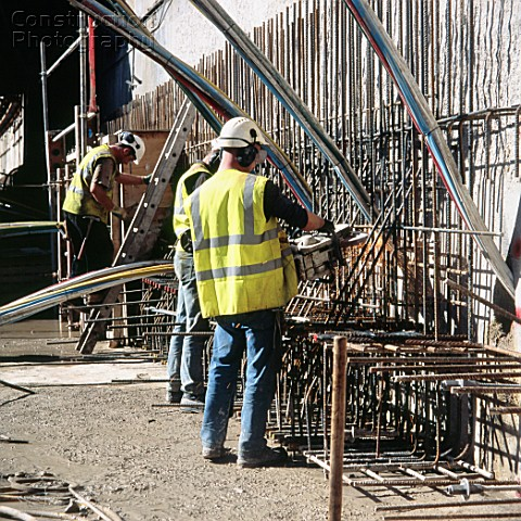 Cutting rebar for the top beam which will be held back by the anchors drilled at an angle into the g