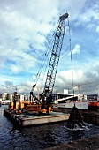 Grab dredging from a barge for the immersed tube tunnel crossing Oslo harbour-new Opera in the background