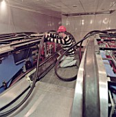 Installing escalator handrail during refurbishment of Angel Underground station. London, United Kingdom.