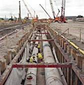 Precast concrete pipes in trench supported by interlocking steel sheet piles and bracing.