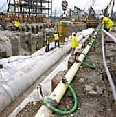 Pouring concrete from hopper to haunch of precast concrete pipes. Dewatering system (green pipes) in operation to remove groundwater during construction. Connahs Quay gas-fired power station, North Wales, United Kingdom.