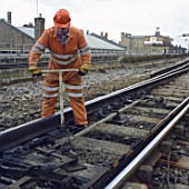 Rail worker adjusting points on railway line.