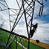 Worker climbing electricity pylon.