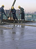 Pouring and compacting in situ reinforced concrete using pump and vibrating poker during reinforced floor slab construction at the Diwa building. London, United Kingdom.