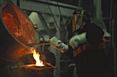 Steel worker in protective clothing working with furnace.