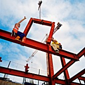 Construction workers assembling steel modular structure during the erection of an office building